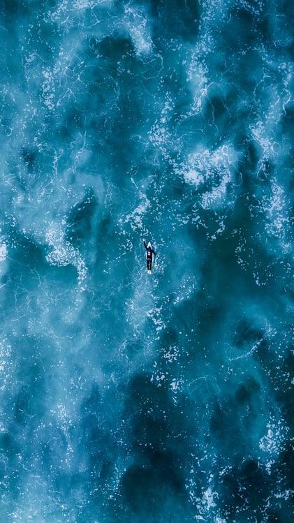 man practising surfing skills in deep water